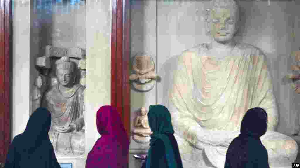 Young women look at statues of Buddha on display in a museum at Taxila in Pakistan's Punjab Province.