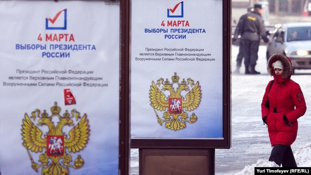 A woman passes by a presidential election campaign posters in Moscow
