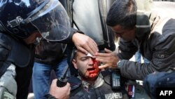 An injured riot police officer is cared for by colleagues in the center of Belgrade.