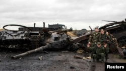 Pro-Russian rebels pose for a picture next to the burnt-out remains of a Ukrainian tank near the village of Novokaterinovka, eastern Ukraine on September 24.
