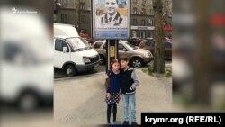 Дети Карачевского рядом с портретом отца на лайтбоксе, Николаев