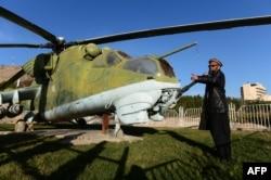 Ауғанстандағы соғыста жоғалған совет сарбазы өзбекстандық Бахретдин Хакимов (шейх Абдулла) өзі жұмыс істейтін музейге қойылған советтік әскери тікұшақтың жанында тұр. Герат, Ауғанстан, 4 ақпан 2015 жыл.