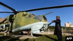 Museum assistant and former Soviet soldier, Sheikh Abdullah, formally known as Bakhretdin Khakimov, stands alongside a Soviet helicopter at the Jihad Museum.