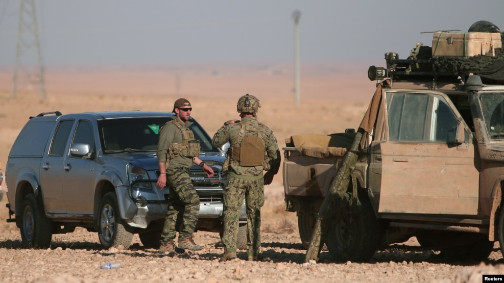 U.S. servicemen stand near military vehicles, north of Raqqa, in Syria earlier this month