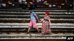 Një migrant nga Siria së bashku me gruan e tij ecin pranë shinave të trenit në qytetin maqedonas të Gjevgjelisë. Fotografi nga arkivi.