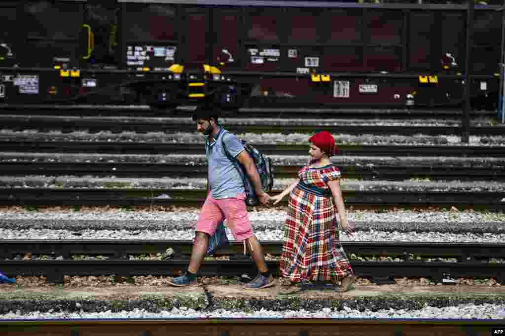 A Syrian migrant and his pregnant wife walk on train tracks towards the town of Gevgelija, on the Macedonian-Greek border. (​AFP/Dimitar Dilkoff)