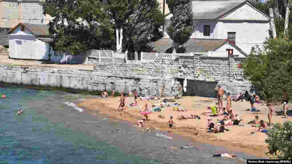 Небольшой песчаный пляж рядом с официальным бетонным пляжем «Ушакова балка» в Нахимовском районе Севастополя. Местные жители называют его пляжем «Угольная бухта»