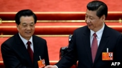 Newly elected President Xi Jinping (right) shakes hands with former President Hu Jintao after Xi was also elected as chairman of the Central Military Commission during the 12th National People's Congress in Beijing on March 14.