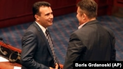 Macedonian Prime Minister Zoran Zeav (left) talks with leftist SDSM party lawmaker Tomislav Tuntev during a session for the ratification of the deal with Greece, in the parliament in Skopje on June 20.