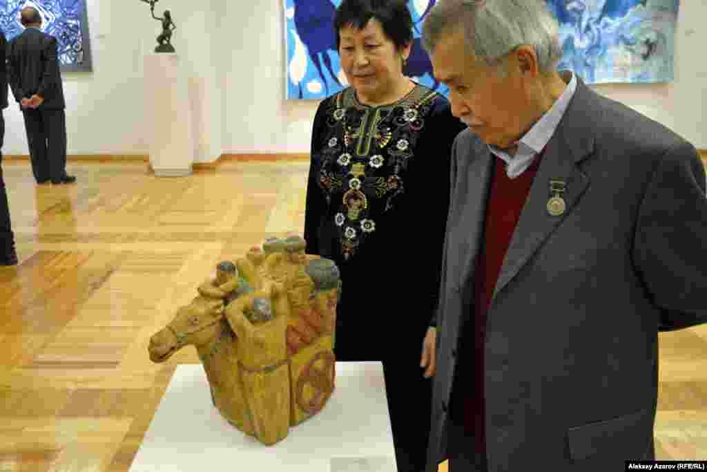 Среди участников выставки – один из старейших художников Казахстана 80-летний Турсын Абуов. Он стоит рядом со своей скульптурной работой «Кочевники» (дерево).