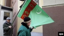 Demonstrators outside the Turkmen Embassy in Moscow hold a Turkmen flag with a black ribbon.