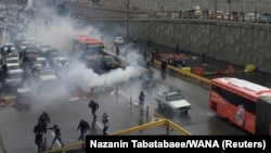 Riot police tries to disperse people as they protest on a highway against increased gas price in Tehran, Iran November 16, 2019.