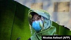 Žena sa zaštitnom opremom u Pekingu, april 2020.
