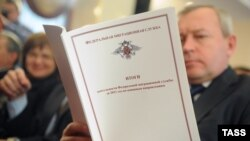 Russia -- A man reads an annual report of Russian Federal Migration Service (FMS) for 2011during a meeting with officials from the Federal Migration Service in Moscow, 26Jan2012