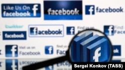 RUSSIA -- A magnifying glass in front of a computer screen showing Facebook logos - generic