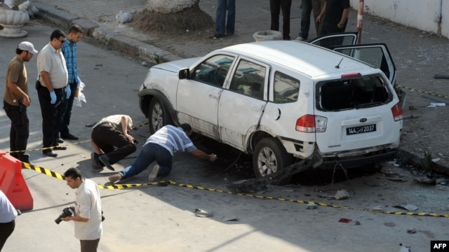 Tunisian police inspect a vehicle that was booby-trapped on July 27 on the outskirts of the Tunisian capital, Tunis.