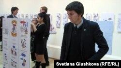 """Посетитель на выставке Mesqueunblog """"Больше чем блог"""" рассматривает комиксы. Астана, 1 ноября 2012 года."""