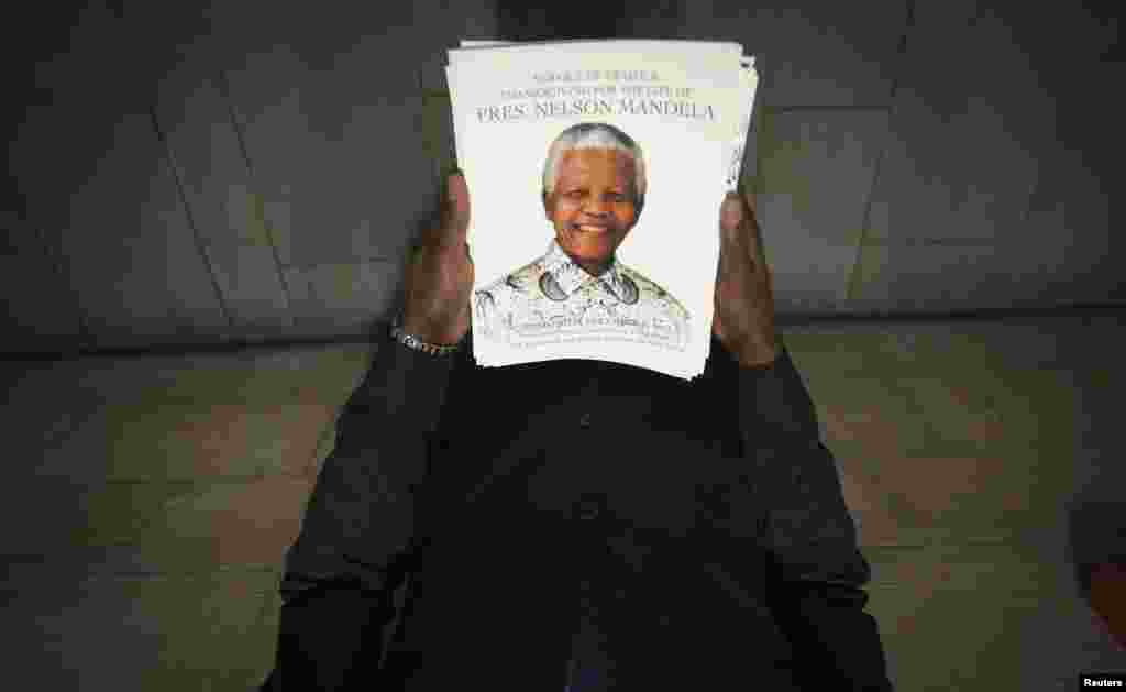 An usher holds programs with the image of Nelson Mandela on the cover before a memorial service for the late South African antiapartheid icon at the Riverside Church in New York. (Reuters/Carlo Allegri)