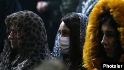 A woman wears a medical mask during a church service in Yerevan, March 1, 2020.