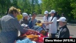 Люди, пришедшие на ярмарку для малоимущих семей, рассматривают вещи. Темиртау, 29 мая 2013 года.