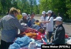 Люди, пришедшие на ярмарку для малоимущих семей, разбирают вещи. Иллюстративное фото. Темиртау, 29 мая 2013 года.