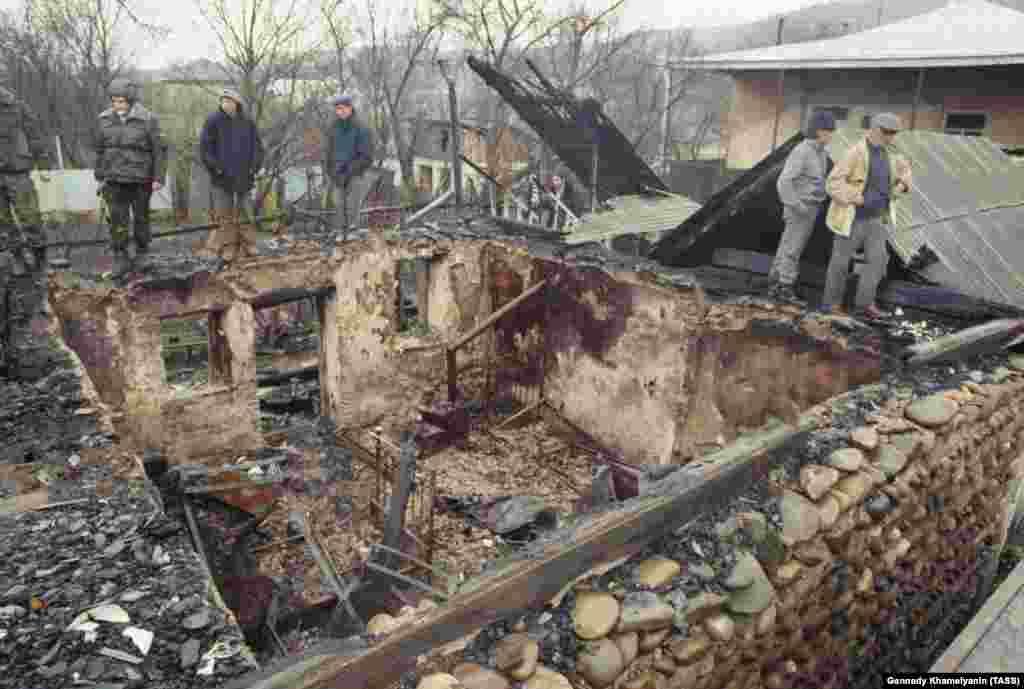 Мужчины осматривают сгоревший дом в грузинском селе Авневи в Южной Осетии, апрель 1991 года. Большая часть этнического насилия происходила в изолированных районах, особенно опасных для нескольких журналистов, которые освещали конфликт
