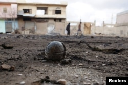 An unexploded cluster bomblet is seen along a street after air strikes by pro-Syrian forces in the rebel held town of al-Ghariyah al-Gharbiyah in Deraa Province on February 11.2016