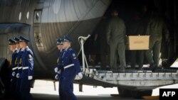 Украинските војници ги поставуваат ковчезите со телата на жртвите во авионите