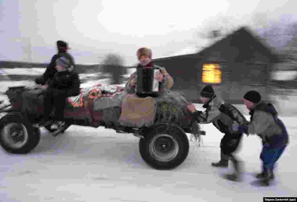 Boys slide behind a cart during Christmas caroling celebrations, known as koliady, in the Belarusian village of Kalachi on January 7, the date marked as Christmas by Orthodox Christians.