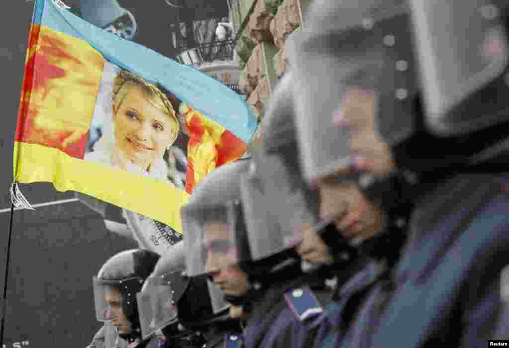 Ukrainian riot police block opposition supporters carrying a flag with a portrait of the jailed former prime minister, Yulia Tymoshenko, from entering city hall during a rally in Kyiv on October 23. (Reuters/Gleb Garanich)