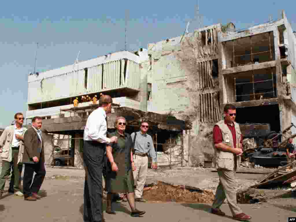 U.S. Secretary of State Madeleine Albright (center) walks past the damaged U.S. Embassy in Dar es Salaam, Tanzania, on August 1998, after a bomb attack credited to Al-Qaeda. At least 11 people were killed.