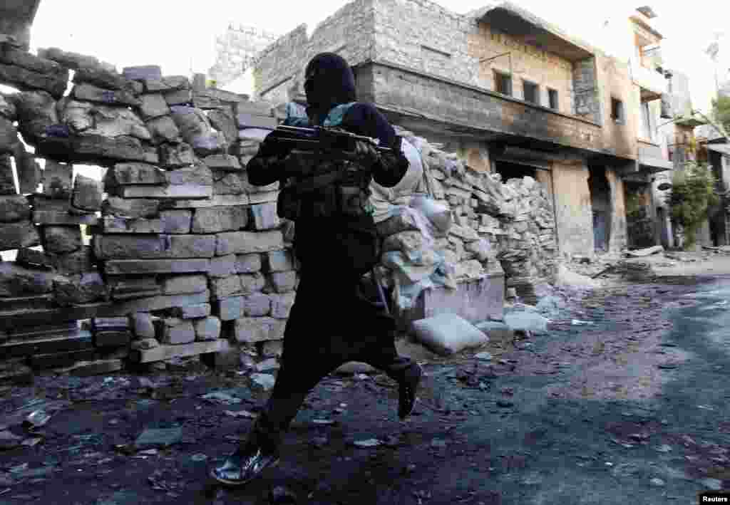 Um Radwan, a female fighter in the Free Syrian Army, runs for cover from snipers loyal to the Syrian regime in Aleppo's Bustan al-Basha district. (Reuters/Muzaffar Salman)