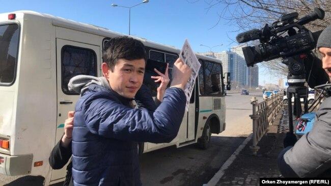 Молодой человек закрывает объектив видеокамеры листом бумаги, мешая оператору Азаттыка вести съемку. Астана, 22 марта 2019 года.