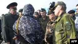 Observatorii militari OSCE încercînd să negocieze cu un militar pro-rus