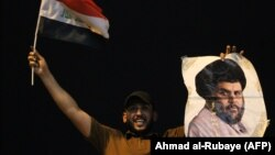 An Iraqi man in Baghdad celebrates with a picture of Shi'ite cleric Muqtada al-Sadr following his strong showing in Iraq's general election earlier this month.