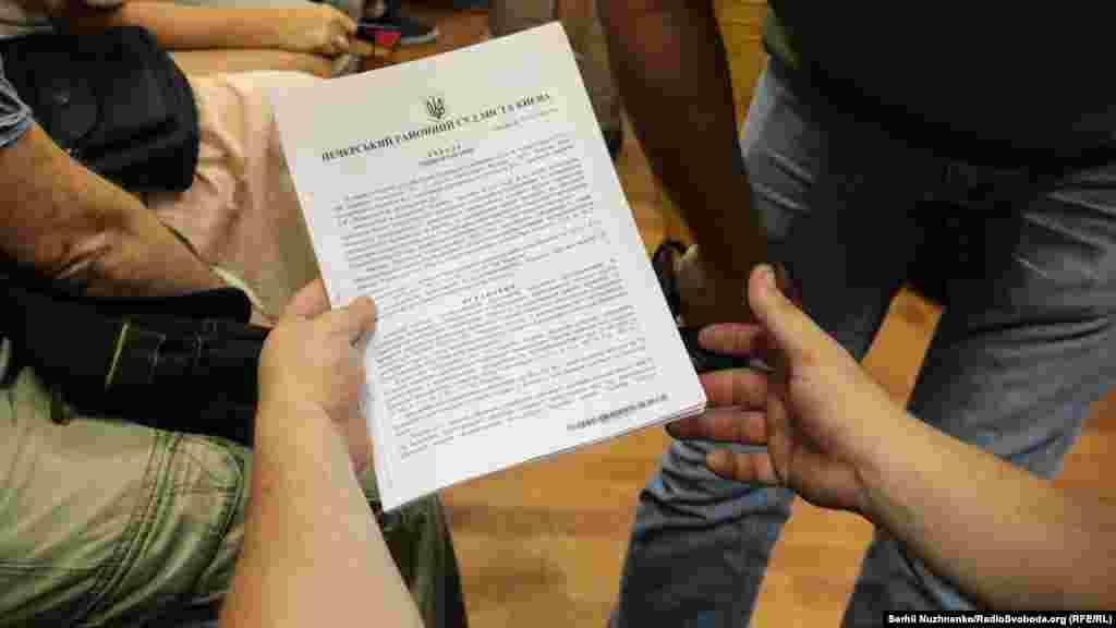 Один із адвокатів тримає ухвалу Печерського районного суду про тримання Лихоліта під вартою терміном 60 днів