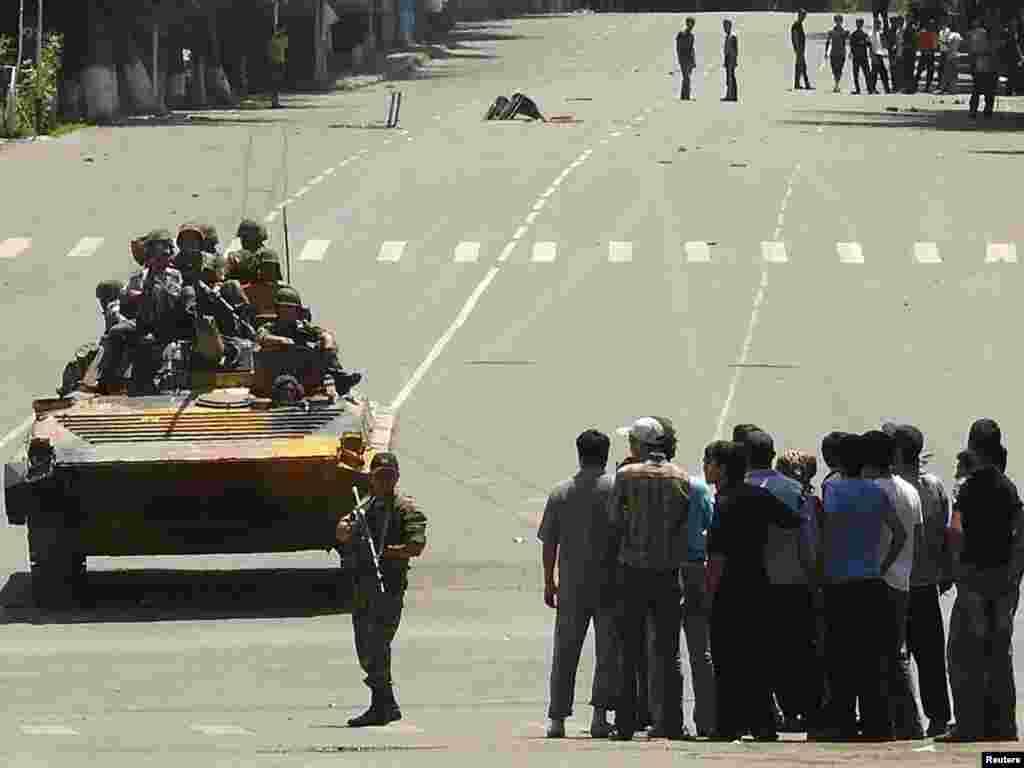 Чопкутталган танктын үстүндө отурган жоокерлер топтошуп турган кишилердин жанынан өтүп бара жатышат. Ош. 11-июнь, 2010-жыл.