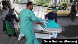A wounded woman arrives for treatment at a hospital after a blast in Kabul on July 25.