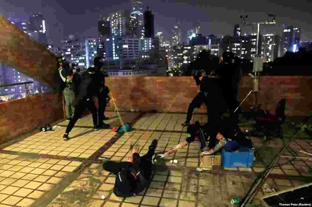 Протестувальники на даху рогаткою кидають каміння в спецпідрозділи поліції під час сутичок біля Гонконгського політехнічного університету, 17 листопада 2019 року