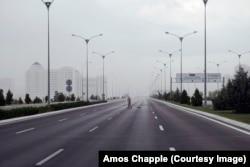 Дворник на одной из крупных автотрасс. Дорога, ведущая из города, пуста перед надвигающимся на город ливнем.
