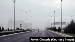 A street cleaner on one of the massive, mostly empty highways running out of Ashgabat as a rainstorm sweeps into the city.
