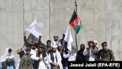 FILE: Afghan civilians carrying Afghan national flag along with Taliban fighters and Afghan army soldiers pose for a photograph during a brief cease-fire in 2018.