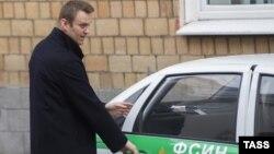 Российский оппозиционер Алексей Навальный садится в машину Федеральной службы исполнения наказаний у здания суда. Москва, 21 октября 2014 года.