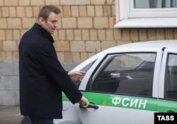 """Алексей Навальный садится в машину ФСИН, чтобы из-под домашнего ареста ехать на заседание суда по делу """"Ив Роше"""", 21 октября 2014 года"""
