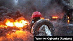 A protester carries tires to add to a burning pile at the site of clashes with riot police.