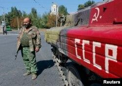 Пророссийский сепаратист стоит у бронемашины с советской символикой. Донецк, 2 сентября 2014 года.