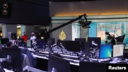 Staff work inside the headquarters of Al Jazeera Media Network, in Doha, June 8, 2017