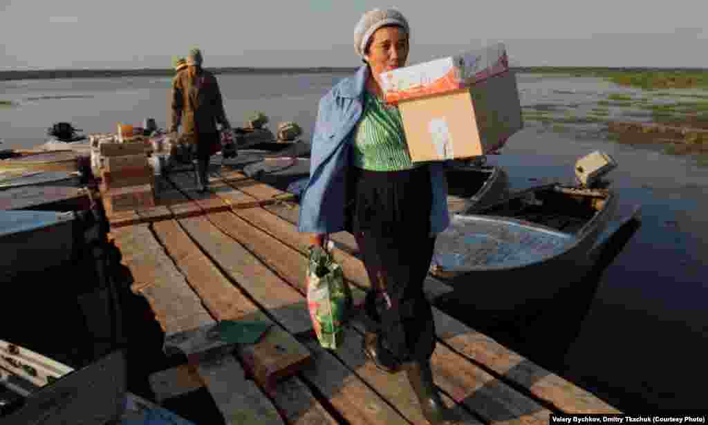 A shop assistant brings supplies to a village shop that have been delivered by boat.