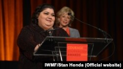 "RFE/RL's Azerbaijani Service correspondent Khadija Ismayilova accepts the 2012 ""Courage in Journalism"" award from the International Women's Media Foundation in New York in October 2012."