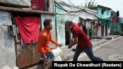 A plainclothes policeman wields his baton against a man as a punishment for breaking the lockdown rules, after India ordered a 21-day nationwide lockdown to limit the spreading of coronavirus disease (COVID-19), in Kolkata on March 25.